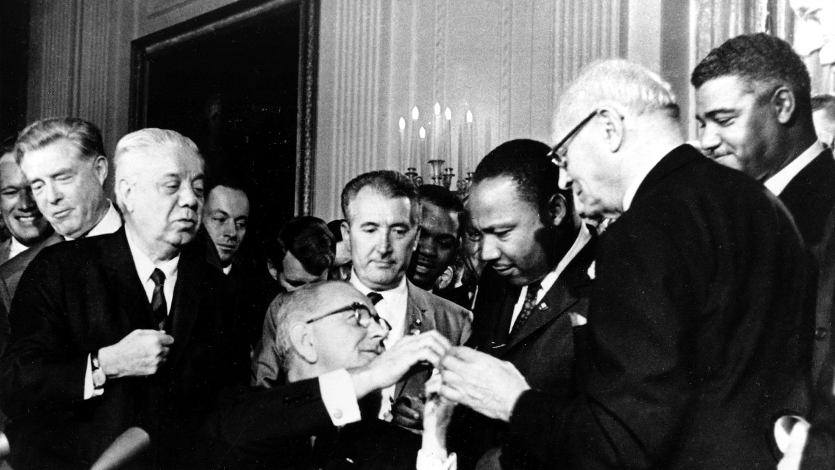 In this July 2, 1964, file photo, President Lyndon B. Johnson reaches to shake hands with Dr. Martin Luther King Jr. after presenting the civil rights leader with one of the 72 pens used to sign the Civil Rights Act in Washington. Surrounding the president, from left, are, Rep. Roland Libonati, D-Ill., Rep. Peter Rodino, D-N.J., Rev. King, Emanuel Celler, D-N.Y., and behind Celler is Whitney Young, executive director of the National Urban League. President Barack Obama was 2-years-old when Johnson signed the Civil Rights Act. Half a century later, the first black president will commemorate what's been accomplished in his lifetime. He'll also recommit the nation to fighting deep inequalities that remain.  (AP Photo)