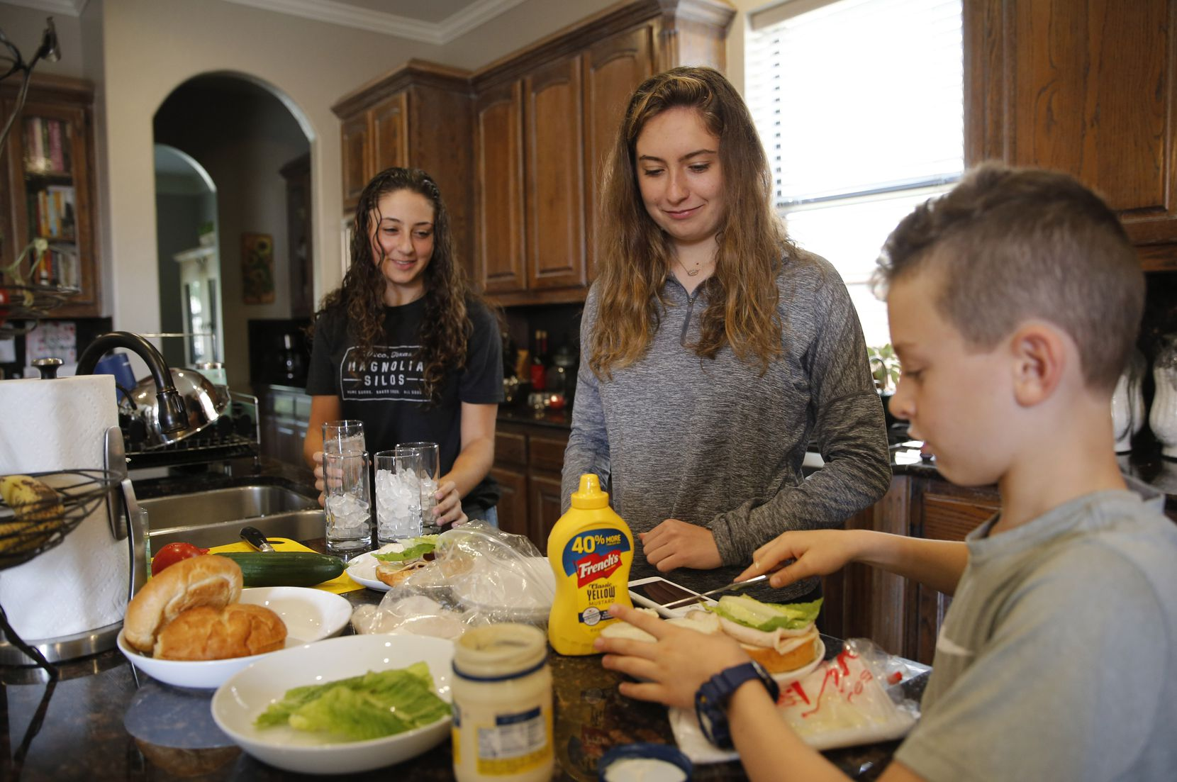 """Heit family siblings Naomi (left), Lilly and Brandon prepare their lunches at home. """"All three of my kids have said repeatedly how they miss their friends and 'there's nothing to do,'"""" says their mother, Jamie Heit. """"They miss school — even my high-schoolers."""""""