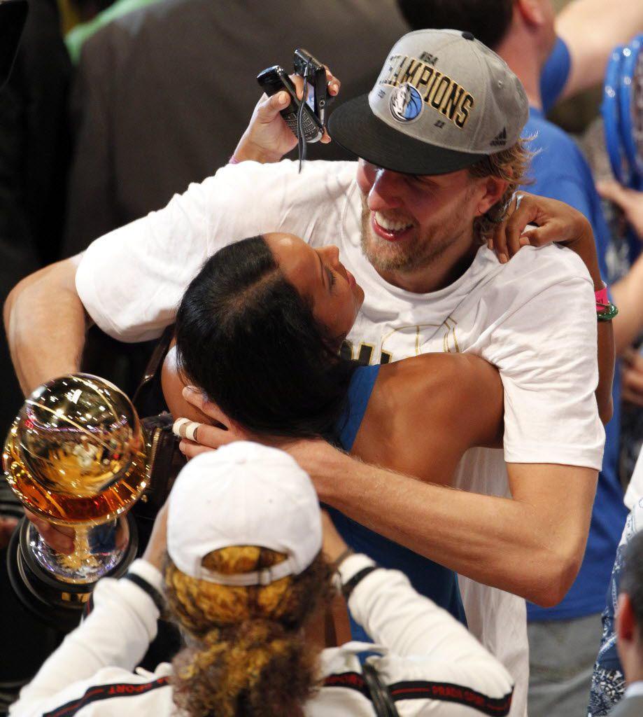 Dallas Mavericks power forward Dirk Nowitzki (41) embraces Jessica Olsson after winning Game 6 of the NBA Finals between the Miami Heat and the Dallas Mavericks at the American Airlines Arena in Miami, Florida, June 12, 2011. The Mavericks won 105-95 to take the title. Nowitzki is holding the Bill Russell NBA Finals MVP trophy which he won. (Vernon Bryant/The Dallas Morning News)