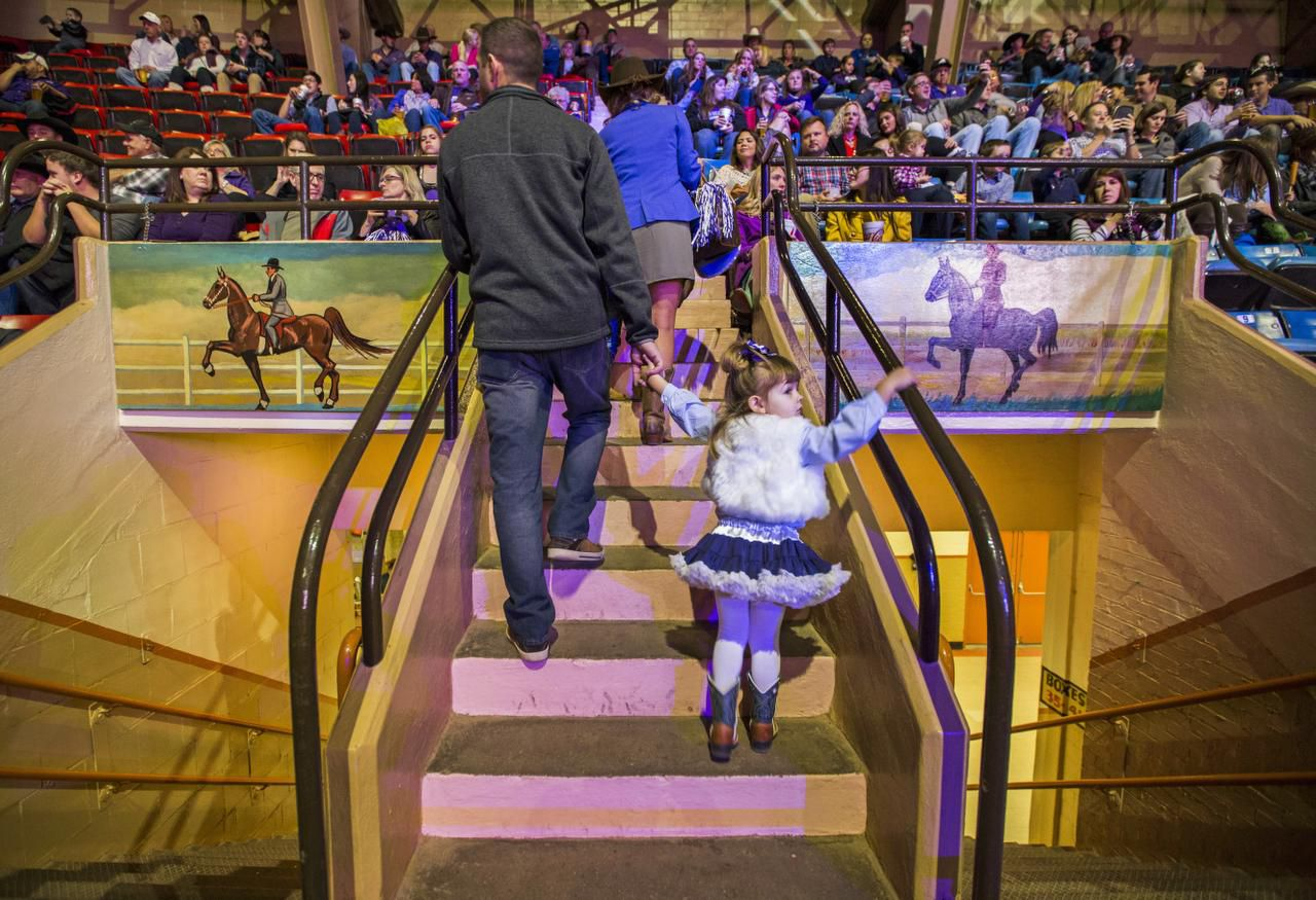 Audience members make their way to their seats between hand-painted murals that hang over each entrance to the historic 1936 Will Rogers Coliseum, home of the Fort Worth Stock Show & Rodeo.