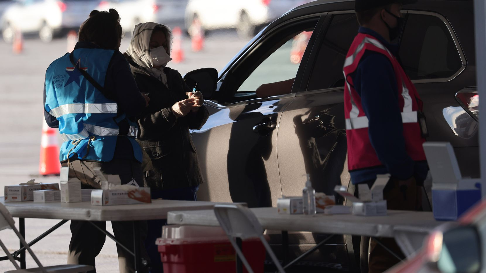 Denton County medical personnel give COVID-19 vaccine shots at a drive-through vaccination clinic at Texas Motor Speedway on Tuesday, February 2, 2021, in Fort Worth. Denton County medical personnel plan to vaccinate 10,000 residents per day.