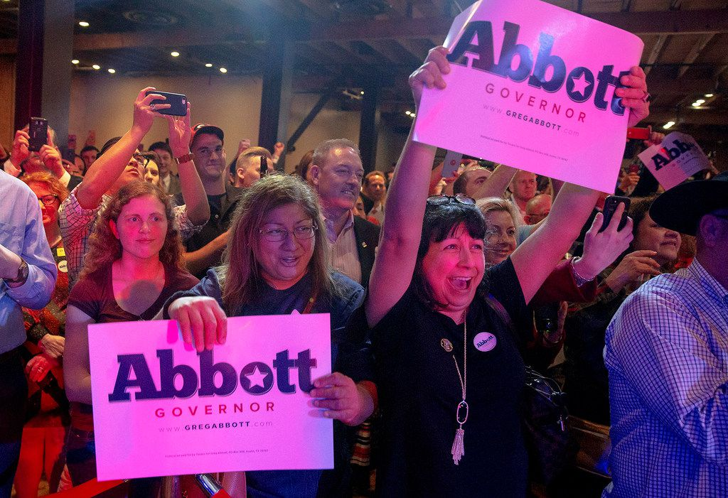 Lisa Vasquez, center left, and Diane Wingert cheer with signs for Greg Abbott as he speaks during the Texas GOP election night party at Brazos Hall in Austin, Texas, on Tuesday, Nov. 6, 2018. (Nick Wagner/Austin American-Statesman via AP)