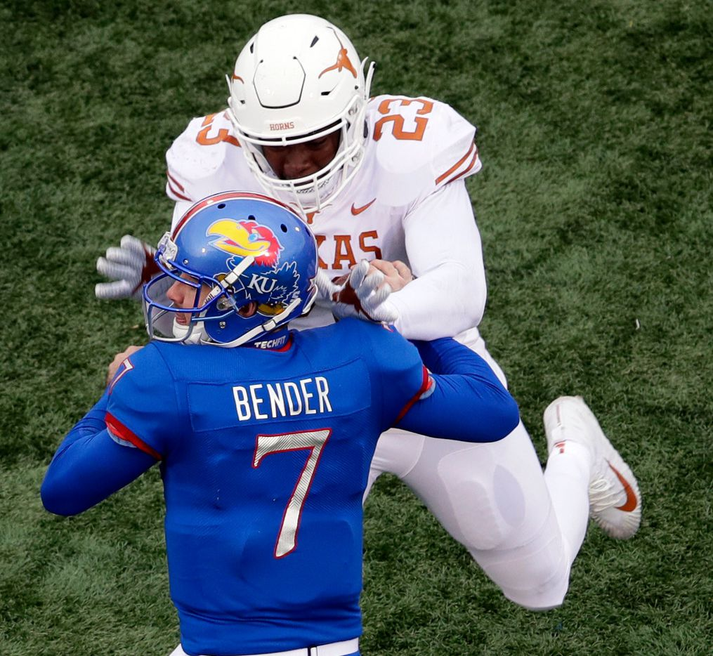 Texas linebacker Jeffrey McCulloch (23) forces a fumble by Kansas quarterback Peyton Bender (7) during the second half of an NCAA college football game in Lawrence, Kan., Friday, Nov. 23, 2018. Texas defeated Kansas 24-17. (AP Photo/Orlin Wagner)