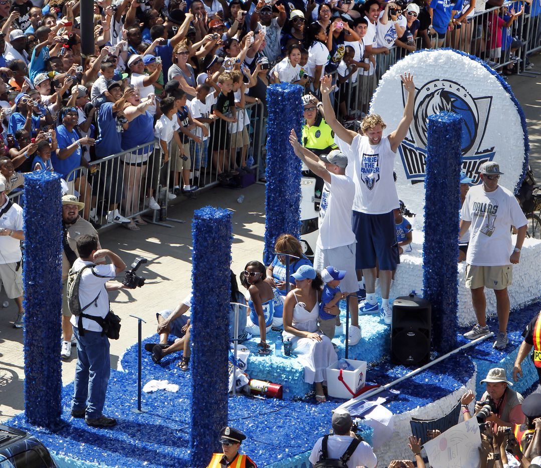 FOR BLOG POST -- Dallas Maverick fans cheer as their teams captains Dirk Nowitzki, Jason Kidd and Jason Terry (hidden behind Dirk) pass during the NBA championship parade june 16, 2011. T Mavericks captured their first NBA title after defeating the Miami Heat. Jim Mahoney/The Dallas Morning NewsThe Dallas Morning News staff photographer John F. Rhodes is at bottom right. / mavsmavsmavs /