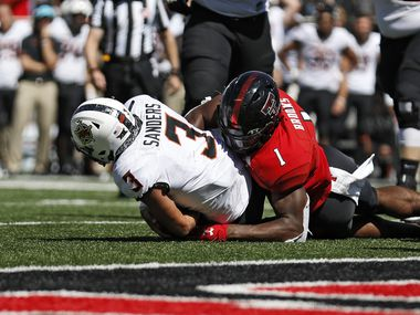FILE - In this Oct. 5, 2019, file photo, Texas Tech's Jordyn Brooks (1) tackles Oklahoma State's Spencer Sanders (3) to stop a two-point conversion during the second half of a game in Lubbock. (AP Photo/Brad Tollefson, File)