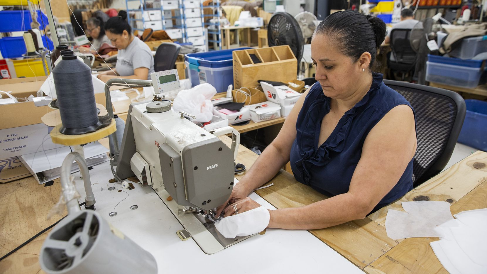 Seamstress Maria Meza makes a mask using fabric normally used as fiber for back cushions at the Leather Sofa Co. factory on March 27, 2020 in Lewisville.