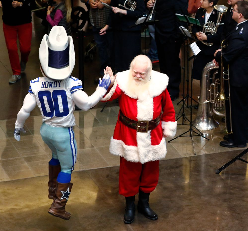 Dallas Cowboys mascot Rowdy gives a high-five to Santa Claus, played by Carl Anderson, during the 2016 Angel Tree Extravaganza for The Salvation Army Angel Tree at NorthPark Center on Black Friday, Nov. 25, 2016, in Dallas.