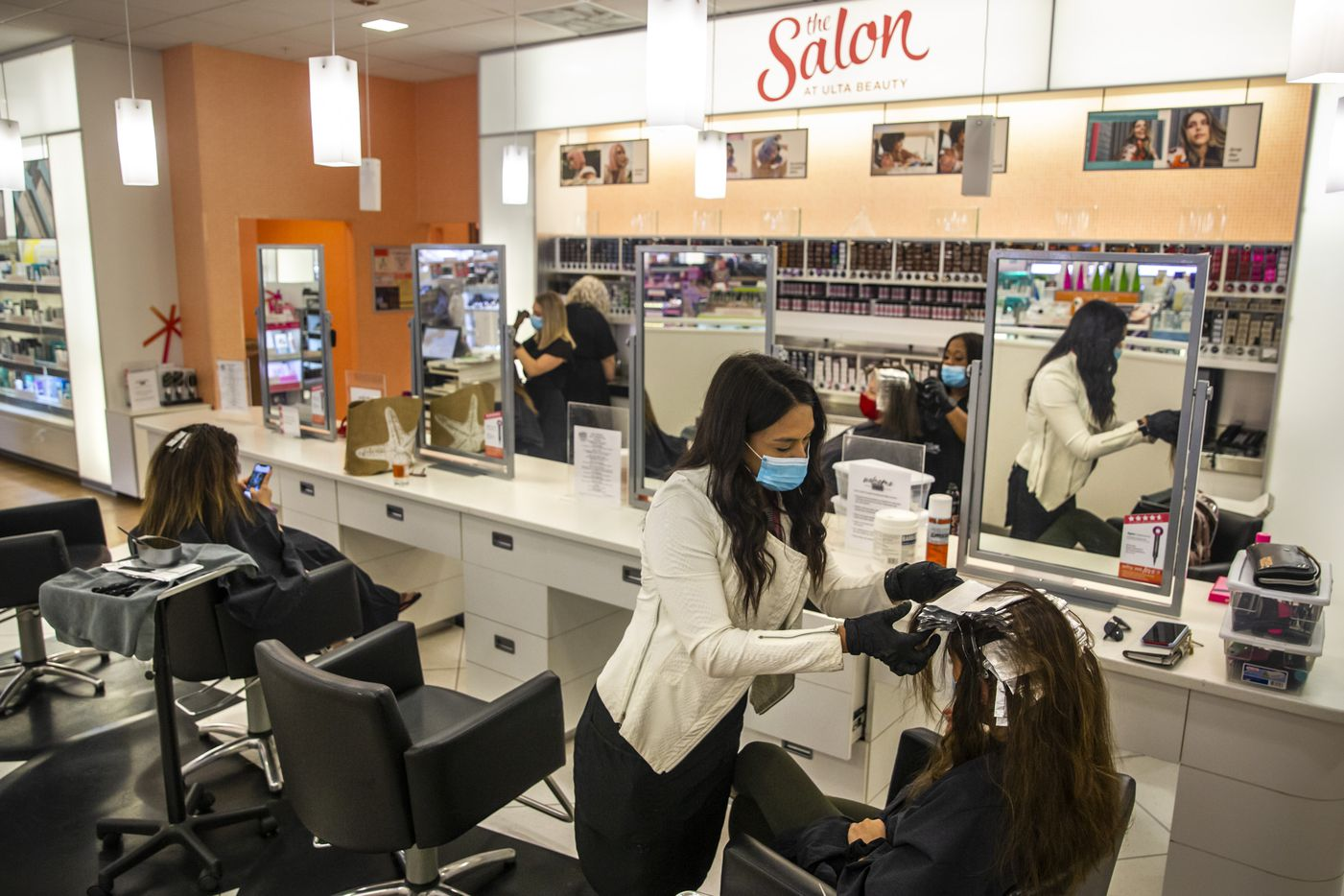 Salon manager Carlie Kirts (second from right) wraps a client's hair in foil at The Salon at Ulta Beauty. The salon can now only take four clients at a time.