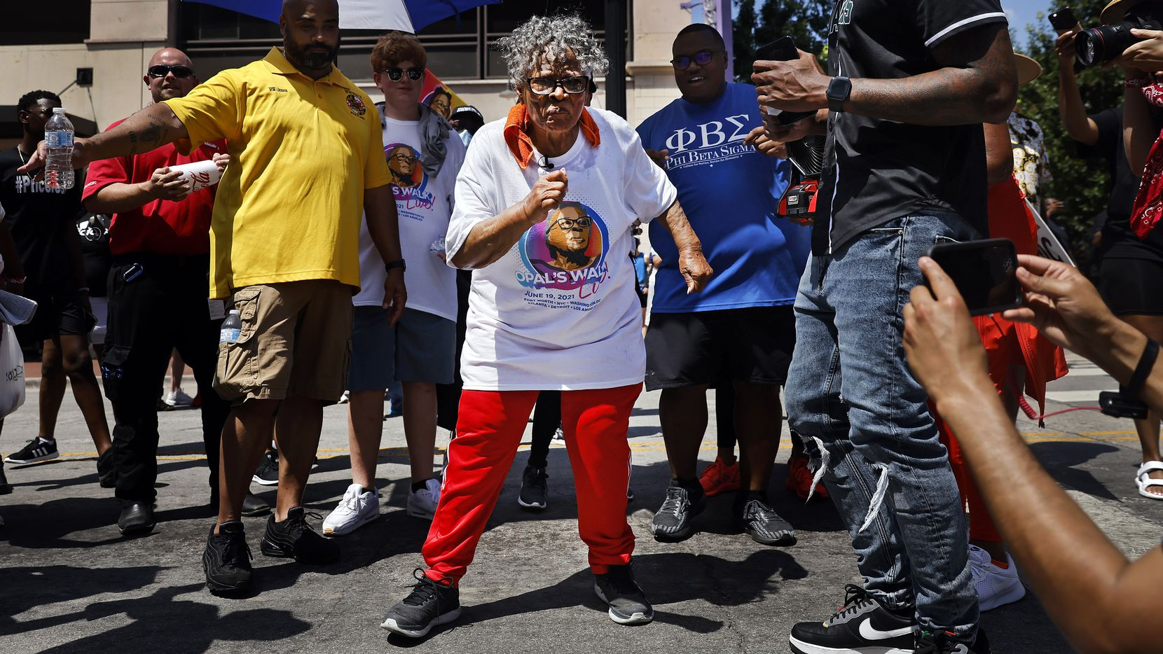 During her walk through downtown Fort Worth, Opal Lee (center) stopped in the middle of Commerce St. and danced to a live music performance for her, Saturday morning, June 19, 2021. For the first time since her dream of Juneteenth being made a national holiday became reality, Ms. Opal Lee led a 2.5 mile caravan from Historic Southside to the Tarrant County Courthouse in downtown Fort Worth. Earlier this week, the civil rights icon stood by President Joe Biden as he signed a law making Juneteenth a federal holiday. At 94 years old, Ms. Opal Lee marked Juneteenth by speaking with supporters at the historic courthouse after cooling down from the hot walk. (Tom Fox/The Dallas Morning News)