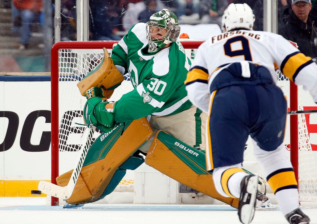 Dallas Stars goaltender Ben Bishop (30) deflects a shot as Nashville Predators left wing Filip Forsberg (9) closes in during the third period of the NHL Winter Classic hockey game at the Cotton Bowl in Dallas, Wednesday, January 1, 2020. The Stars came back to win, 4-2.