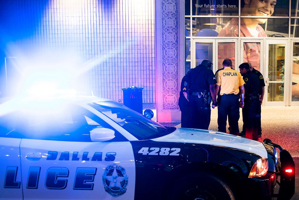 At 8:53 p.m., five minutes before the shootings began exactly one year earlier, Dallas Police Department officers join Dallas County Community College District police in payer in front of the Lamar Street entrance to El Centro College between Elm and Main on the anniversary of the attack which killed five police officers at the same location on Friday, July 7, 2017, in Dallas. (Smiley N. Pool/The Dallas Morning News)