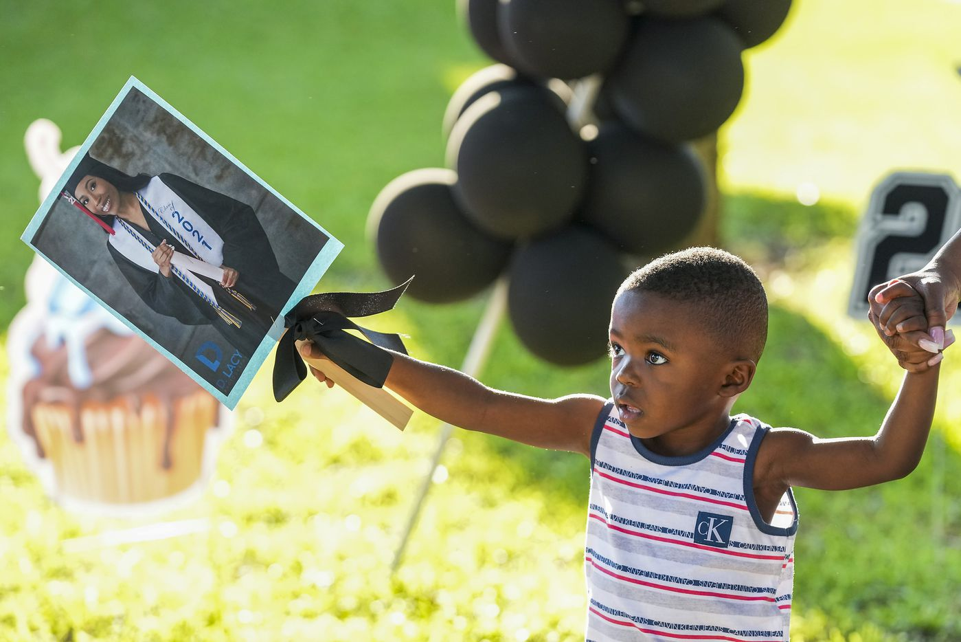 Antwone Anthony, 3, carries a senior photo of his cousin Eryn Fayson as well wishers arrive to celebrate Eryn's graduation from Booker T. Washington HSPVA on Saturday, June 19, 2021.