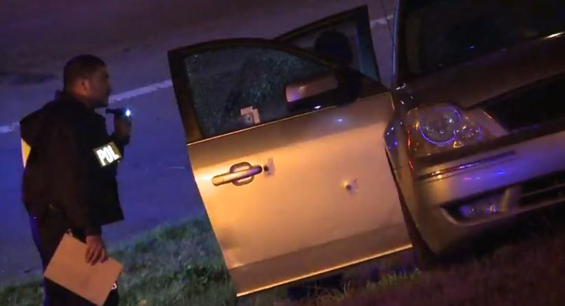 Dallas police examine a car with bullet holes in it after a crash occurred Monday night near the border of Lake Highlands and far northeast Dallas.