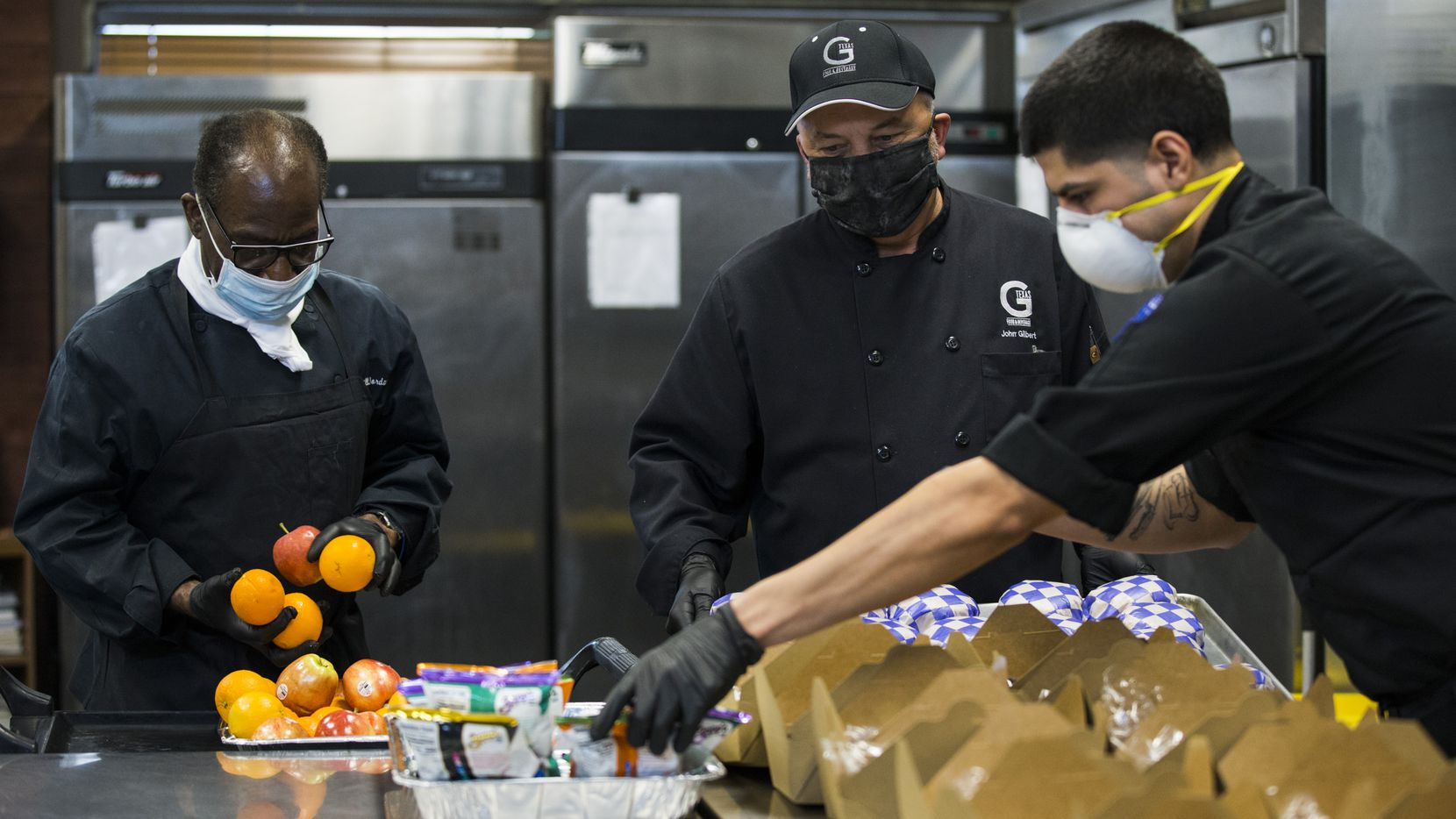 John Gilbert (center), owner of G-Texas Custom Catering, and employees Bill Jordan (left) and Nieves Perales (right) pack box lunches for Austin Street Shelter on Saturday, April 11, 2020 at G-Texas Custom Catering in Dallas. (Ashley Landis/The Dallas Morning News)