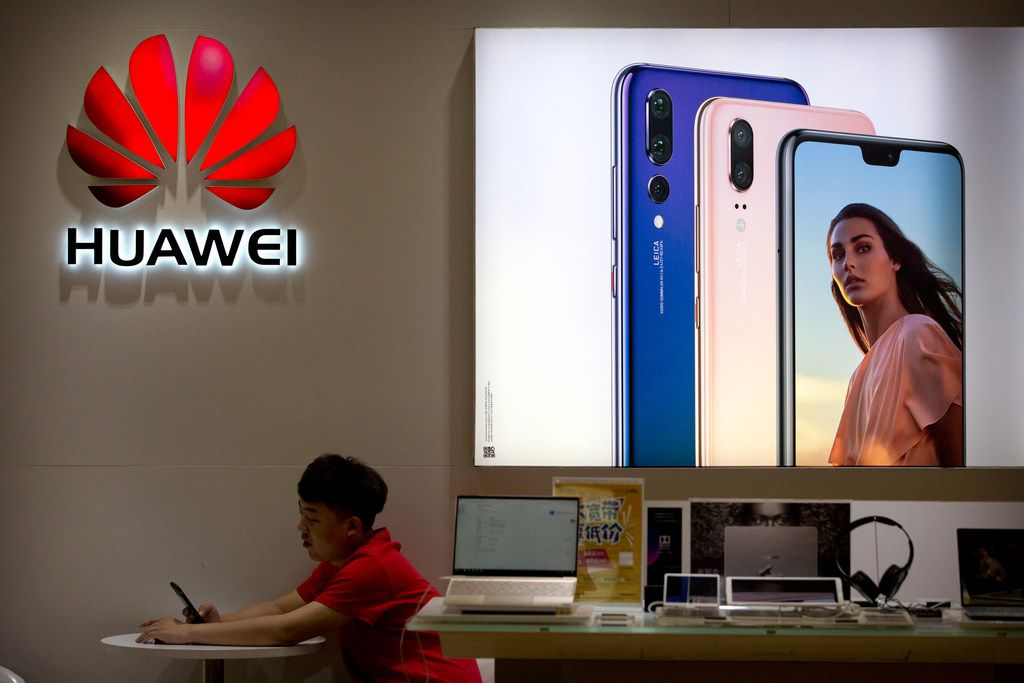 A sales clerk looks at his smartphone in a Huawei store at a shopping mall in Beijing on July 4. China has produced success stories including Huawei Technologies Ltd., the biggest global seller of switching gear for phone companies and the No. 3 smartphone brand. The company has developed its own Kirin line of chip sets to power some of its phones, reducing reliance on U.S.-based Qualcomm Corp.'s Snapdragon and other foreign suppliers.