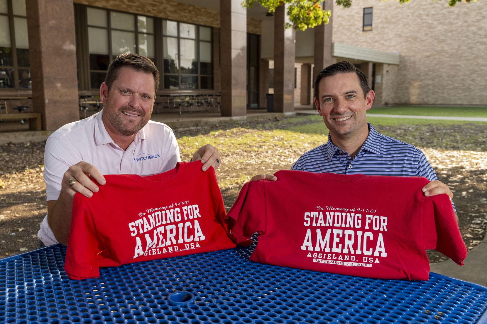 """Josh Rosinski (left) and Cole Robertson display a pair of original T-shirts sold for Texas A&M's """"Red, White and Blue Out"""" game following the attacks on Sept. 11, pictured on Thursday, Sept. 2, 2021, in Richardson, Texas. Rosinski and Robertson were part of a group of students that led an effort to have fans at Kyle Field don red, white and blue T-shirts in a show of national unity."""