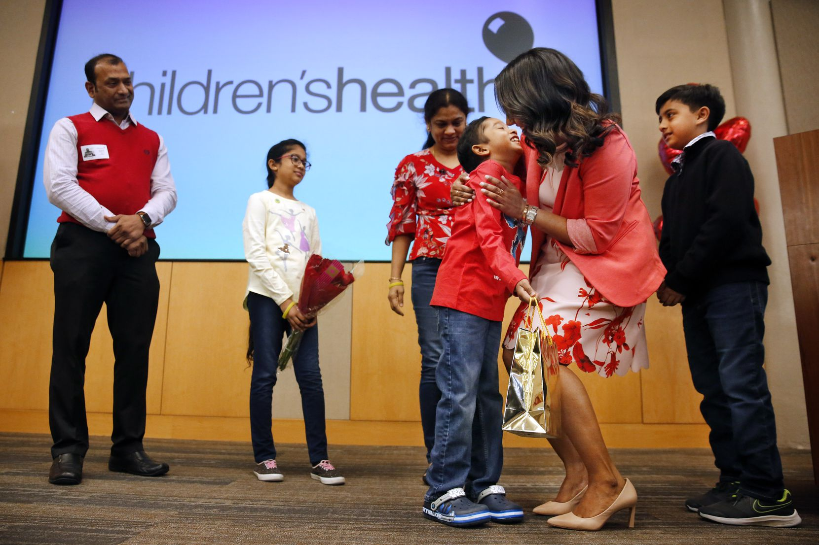 Bone marrow recipient Akshaj Nagilla gives his donor, Dr. Prasanthi Ganesa (second from right), a hug as they meet for the first time at Children's Medical Center Dallas, Friday, February 14, 2020.  (Tom Fox/The Dallas Morning News)