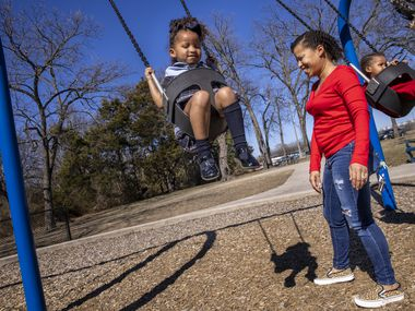 """Marchelle Simpson (center) pushes her children, Kyla, 4 (left) and Kyre, 2, on the swings at Grimes Park on Tuesday, Feb. 23, 2021, in DeSoto, Texas. """"It sure is a lot different than how it was last week!"""" Simpson said."""