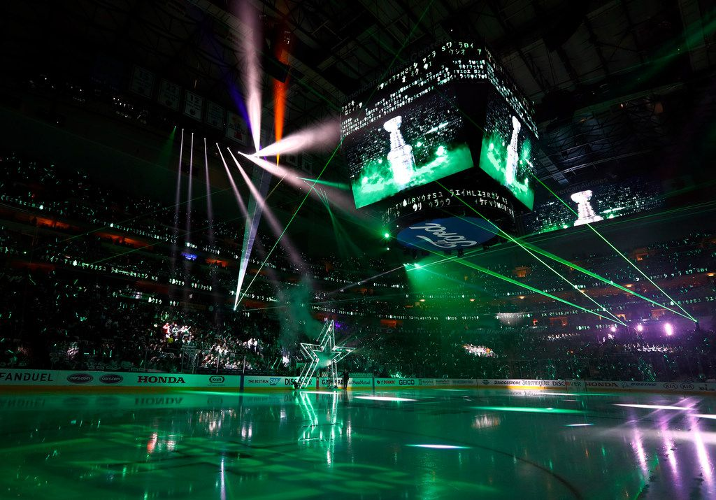 Fans look on during a laser light show before team introductions in Game 4 in an NHL hockey first-round playoff series between the Nashville Predators and Dallas Stars in Dallas, Wednesday, April 17, 2019. (AP Photo/Tony Gutierrez)