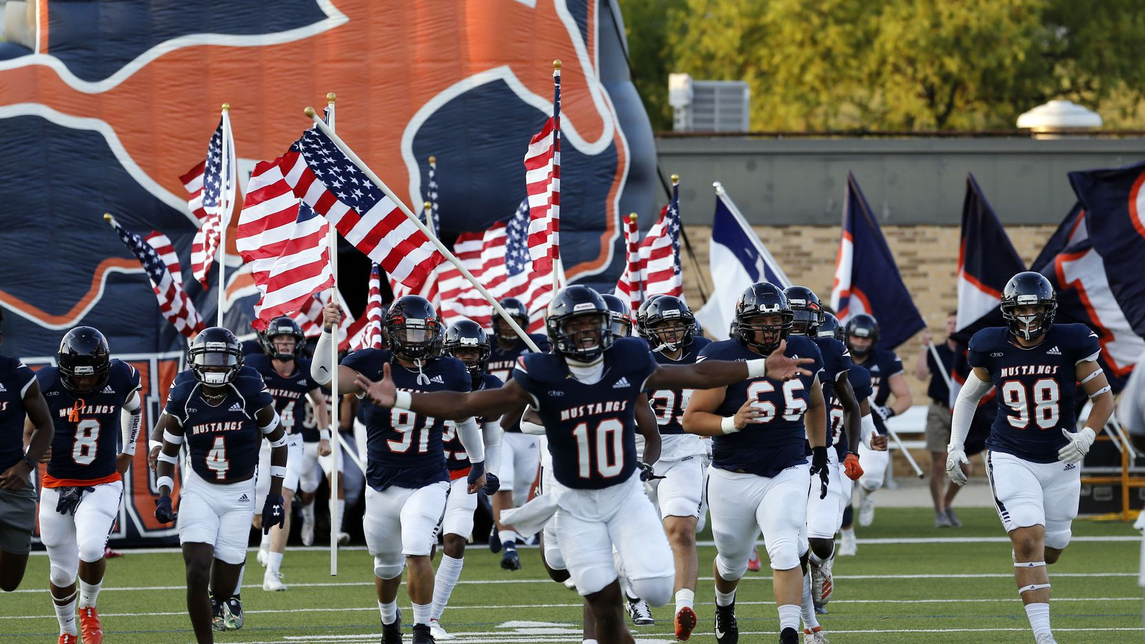 The Sachse High Mustangs run onto the field, led by QB Alex Orji (10), before the first half of a high school football game against Denton Braswell at Homer B Johnson Stadium in Garland on Thursday, September 9, 2021.