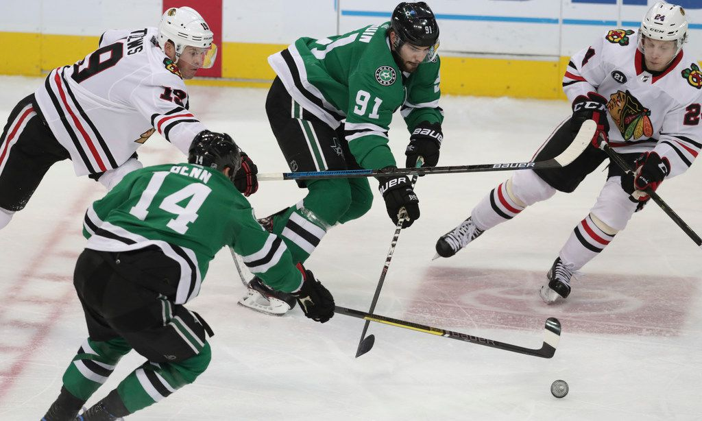 Chicago Blackhawks centers Dominik Kahun (24) and Jonathan Toews (19) battle for the puck against Stars center Tyler Seguin (91) and left wing Jamie Benn (14) during the second period of a game in Dallas on Thursday, Dec. 20, 2018. (AP Photo/LM Otero)