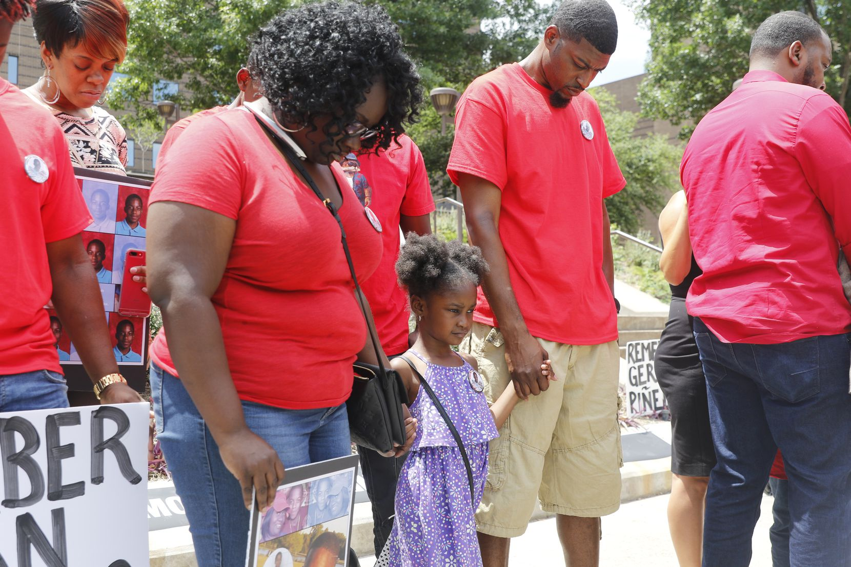Jordan Edwards' step-mom Charmaine Edwards, sister Korrie Edwards, 4, and dad, Odell Edwards, bow their heads in prayer in front of the Frank Crowley Courts Building Saturday May 13, 2017 during a rally remembering Jordan and others killed by police.
