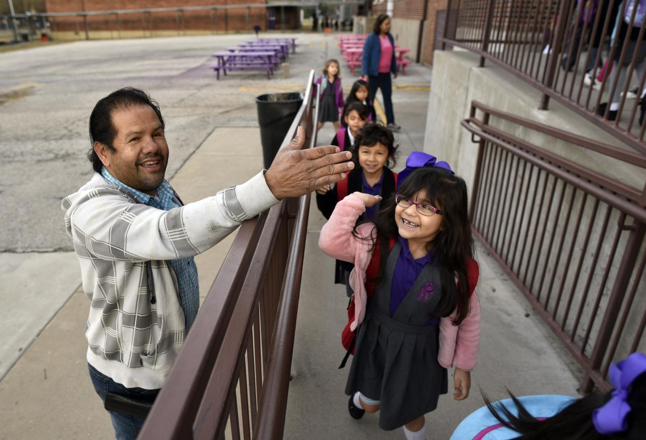 Marco Medina saluda a loas estudiantes de Solar Prep. Medina y su esposa Maritssa son voluntarios para dirigir el tráfico escolar en la escuela. BEN TORRES/DMN