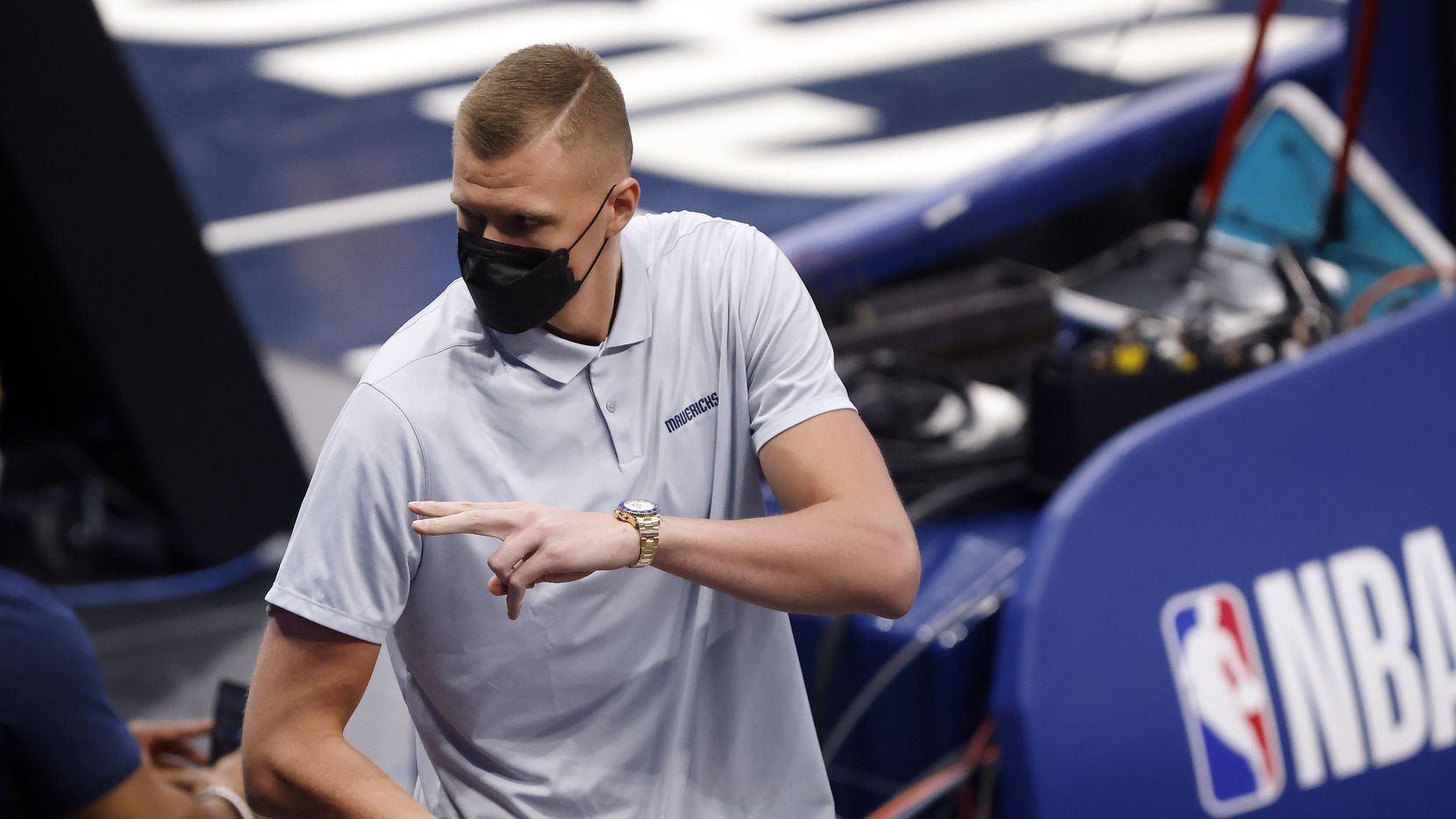 Dallas Mavericks injured center Kristaps Porzingis waves to friends as he steps into the arena during the first half against the Boston Celtics at the American Airlines Center in Dallas, Tuesday, February 23, 2021.
