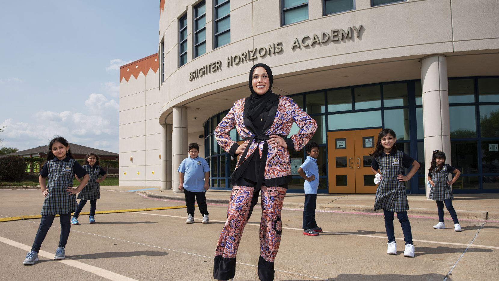 Alaa Ammuss, 31, of Plano, an alumna of Brighter Horizons Academy in Garland, is surrounded by students wearing the uniforms she designed.