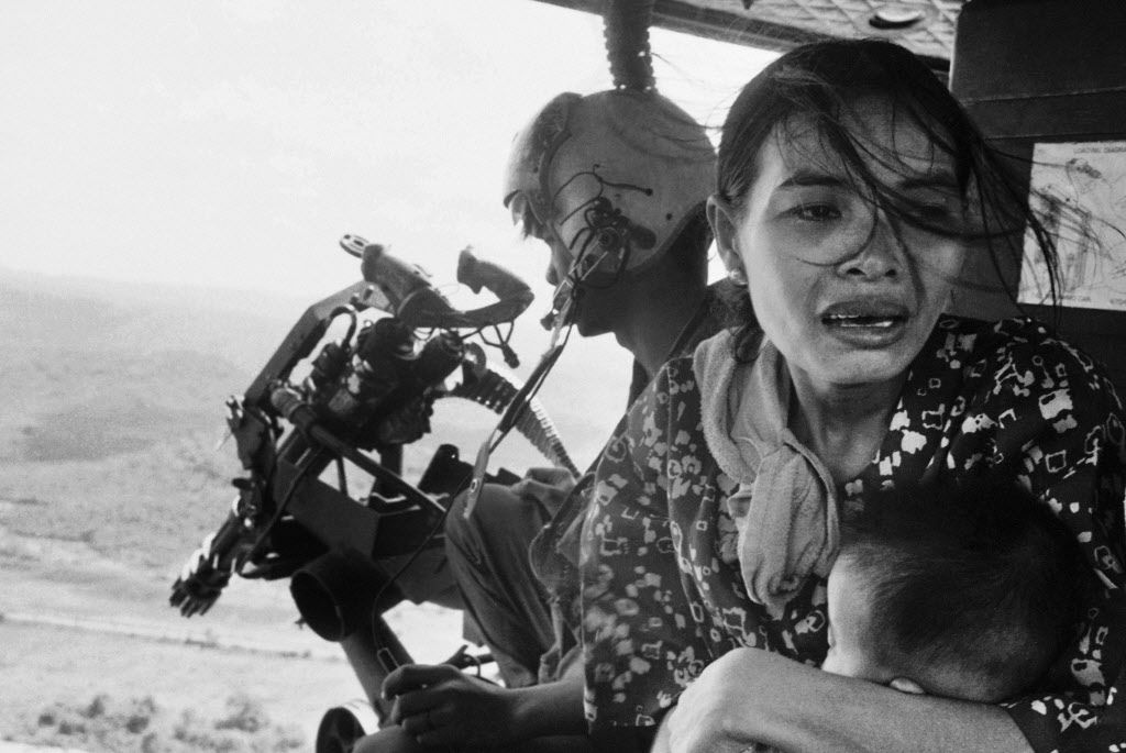 In this March 22, 1975 file photo, a refugee clutches a baby as a government helicopter gunship carries them away near Tuy Hoa, Vietnam, 235 miles northeast of Saigon. They were among thousands fleeing from Communist advances.