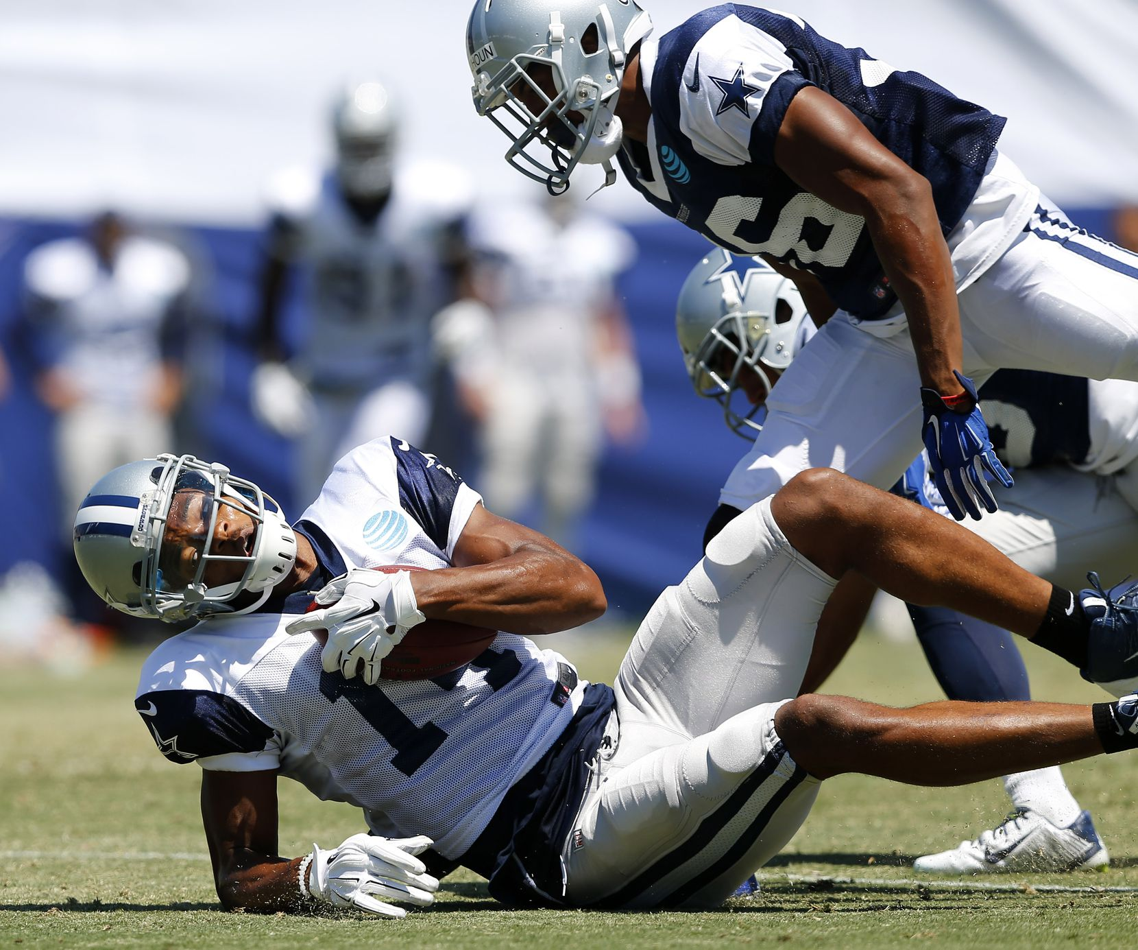 Dallas Cowboys wide receiver Rodney Smith (14) takes a shot from defensive back Arjen Colquhoun (36) after making a catch during morning practice at training camp in Oxnard, California, Thursday, August 11, 2016. (Tom Fox/The Dallas Morning News)