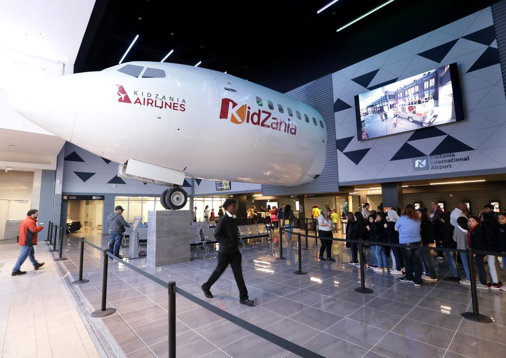 Children 6-14 enter KidZania through an airport with real plane parts.