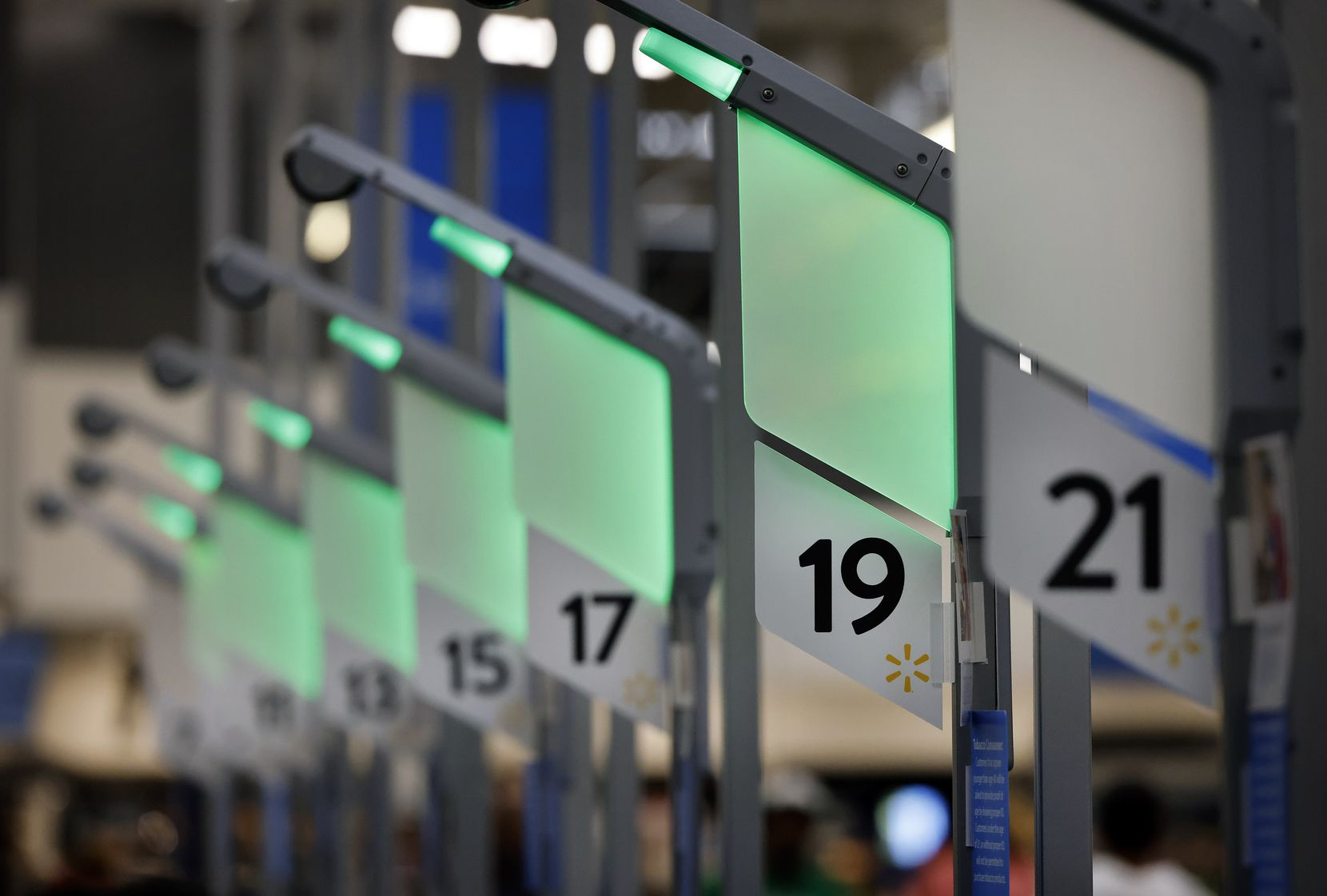 Green lights at self checkout stations inform customers of an open scanner at the Walmart Supercenter on Ohio Drive in Plano, Texas.