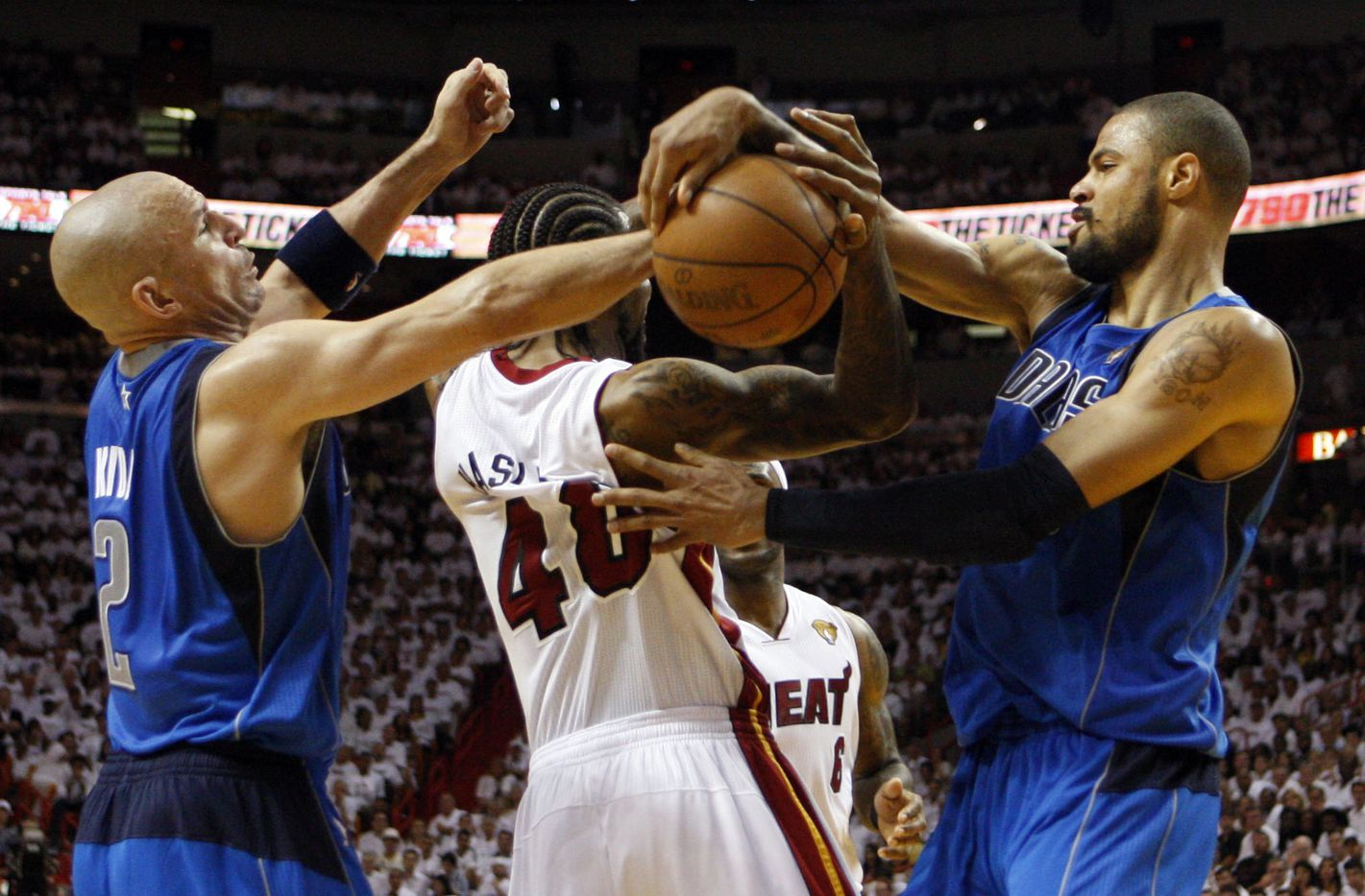 Dallas Mavericks point guard Jason Kidd (2) and Dallas Mavericks center Tyson Chandler (6) strip the ball from Miami Heat power forward Udonis Haslem (40) during the third quarter of play in Game 1 of the NBA Finals at American Airlines Arena in Miami, on May 31, 2011. (Vernon Bryant/The Dallas Morning News)