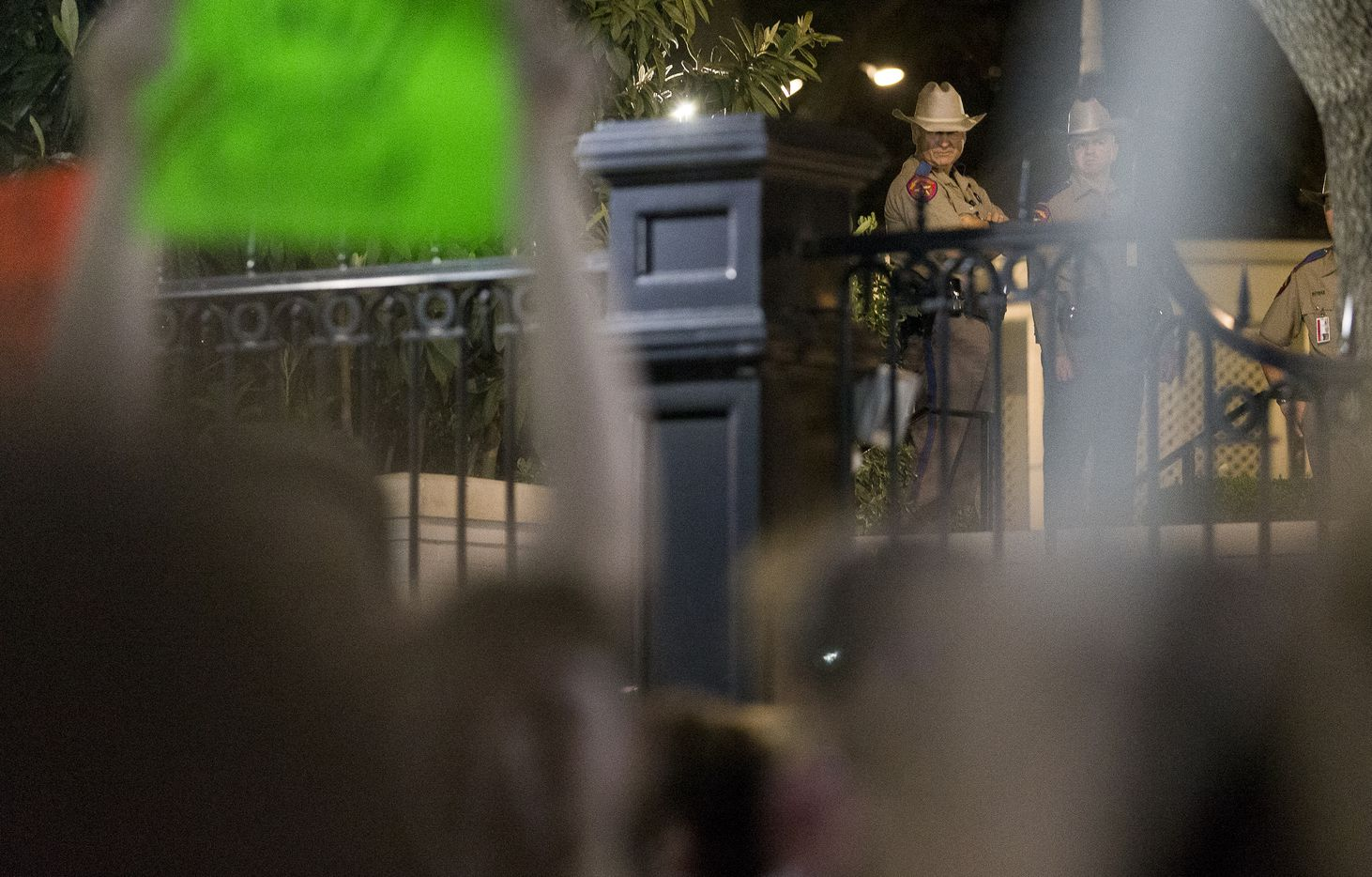 Texas Department of Public Safety Troopers watch as supporters of the LGBTQ community gather for a dance party outside the Governor's Mansion in Austin on Thursday, Feb. 23, 2017.