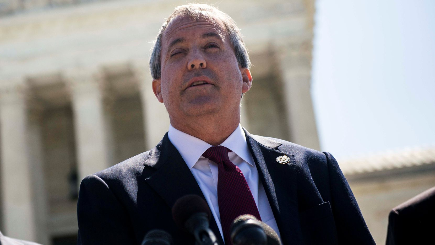 Texas Attorney General Ken Paxton stands outside the U.S. Supreme Court building in 2016. Paxton released an opinion on Wednesday  clarifying that felons could not run for office or serve as an elected official unless they'd received some kind of clemency from the governor or a judge.