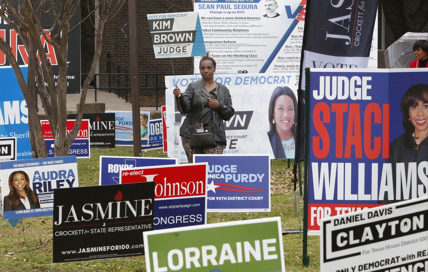 "Cheryl Miller holds a ""Kim Brown for Judge"" sign as she stands with other candidates signs in the parking lot of  Dallas County Government Center at the corner of Beckley Ave and Twelfth St, Precinct 5, Tuesday morning, March 3, 2020 in Oak Cliff. Polls will be open from 7 a.m. to 7 p.m. on Super Tuesday."