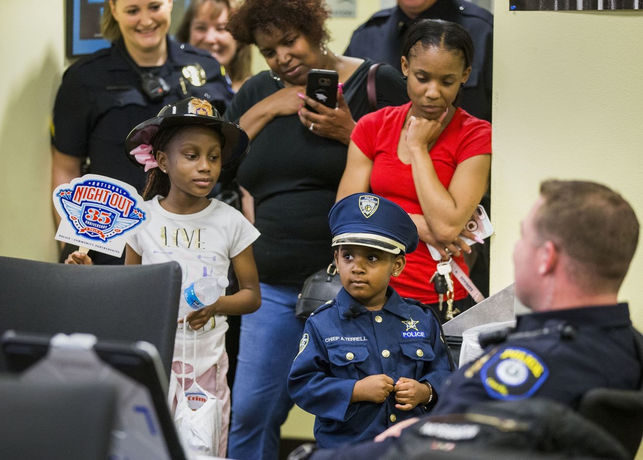 With her family behind her, 4-year-old Ah'Maya Terrell visits with Officer Jon Morrison during a tour of the Cedar Hill Police Department.