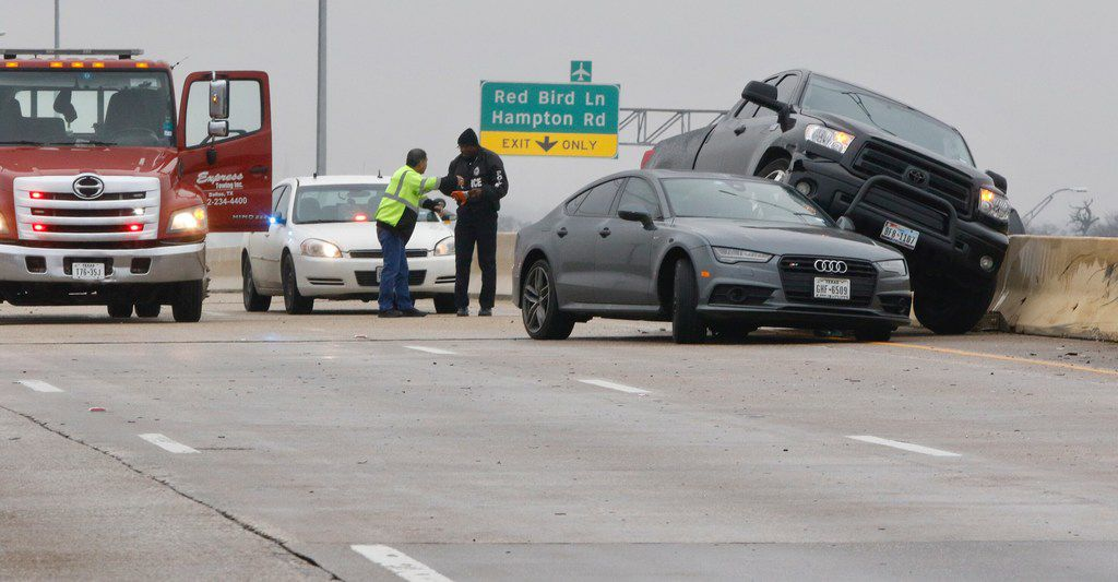 Richard Garay, left, of Express Towing, Inc., talks to Dallas Police officer J. W. Jacobs, right, after he arrived at the scene of the wreck on the southbound lanes Hwy. 67 over Camp Wisdom Road on February 28, 2019 in Dallas. Freezing temperature and wet conditions overnight led to icy roads, causing dozens of accidents.