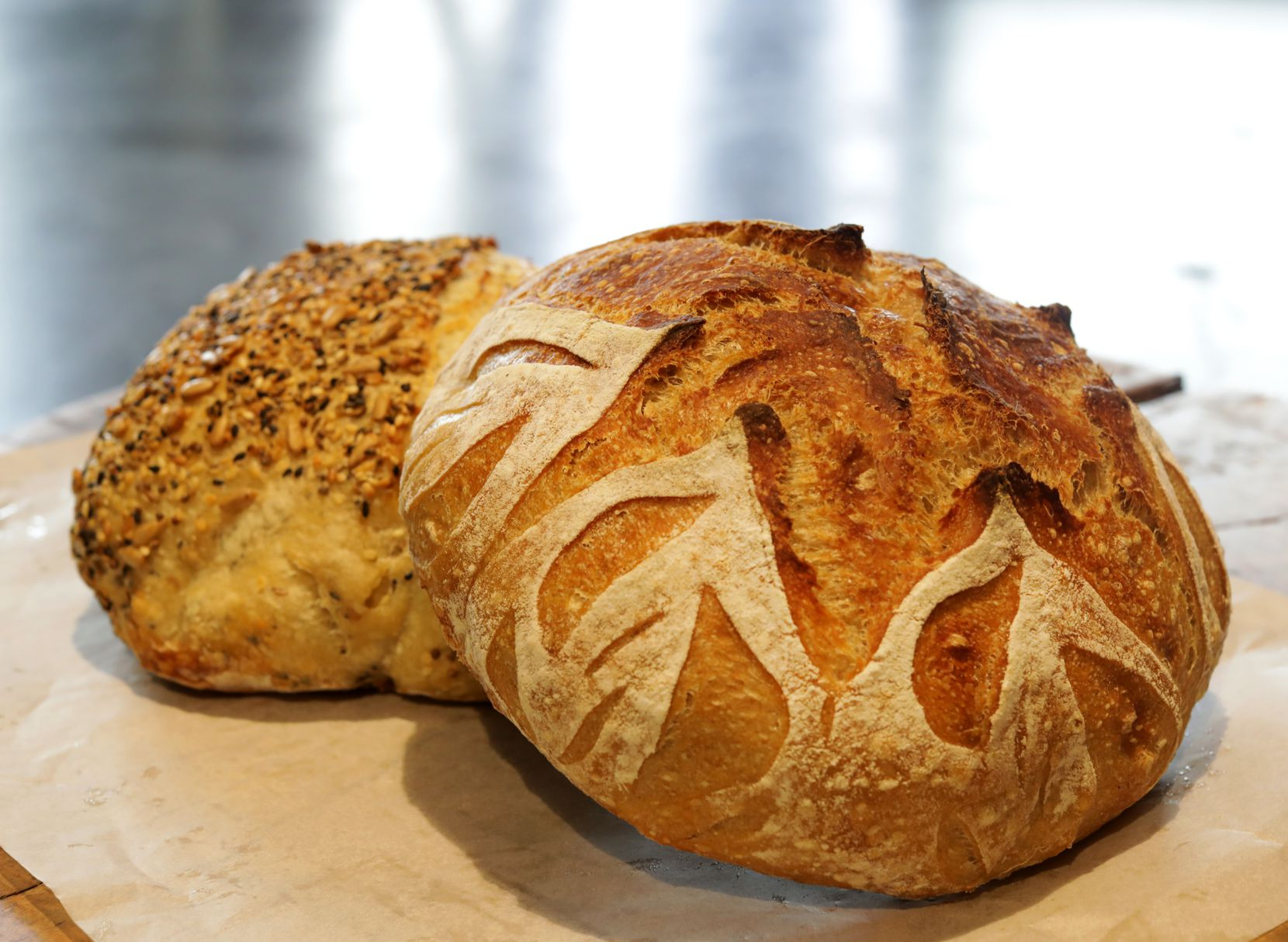 The Seeded Semolina, left, and Einkorn Mesquite sourdough bread offered by Girl With Flour during pop-up shop events at Mudleaf Coffee in Plano