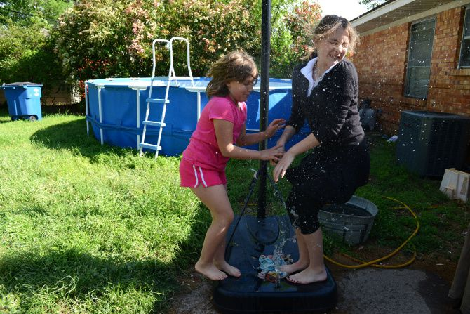 Sisters Zadie (left) and Zoe Wittrock splash water from the base of a basketball goal in the backyard of the family's home in Old Lake Highlands. The neighborhood was rated the best area for families with children in East Dallas.  ROSE BACA/neighborsgo staff photographer