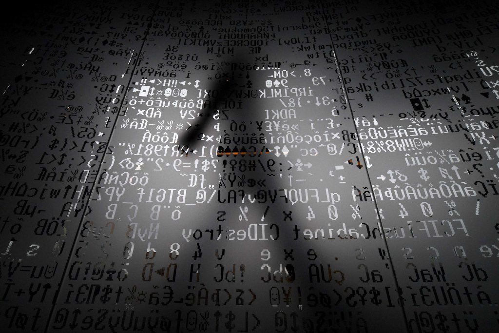TOPSHOT - A picture taken on October 17, 2016 shows an employee walking behind a glass wall with machine coding symbols at the headquarters of Internet security giant Kaspersky in Moscow. / AFP PHOTO / Kirill KUDRYAVTSEV / TO GO WITH AFP STORY BY Thibault MARCHANDKIRILL KUDRYAVTSEV/AFP/Getty Images