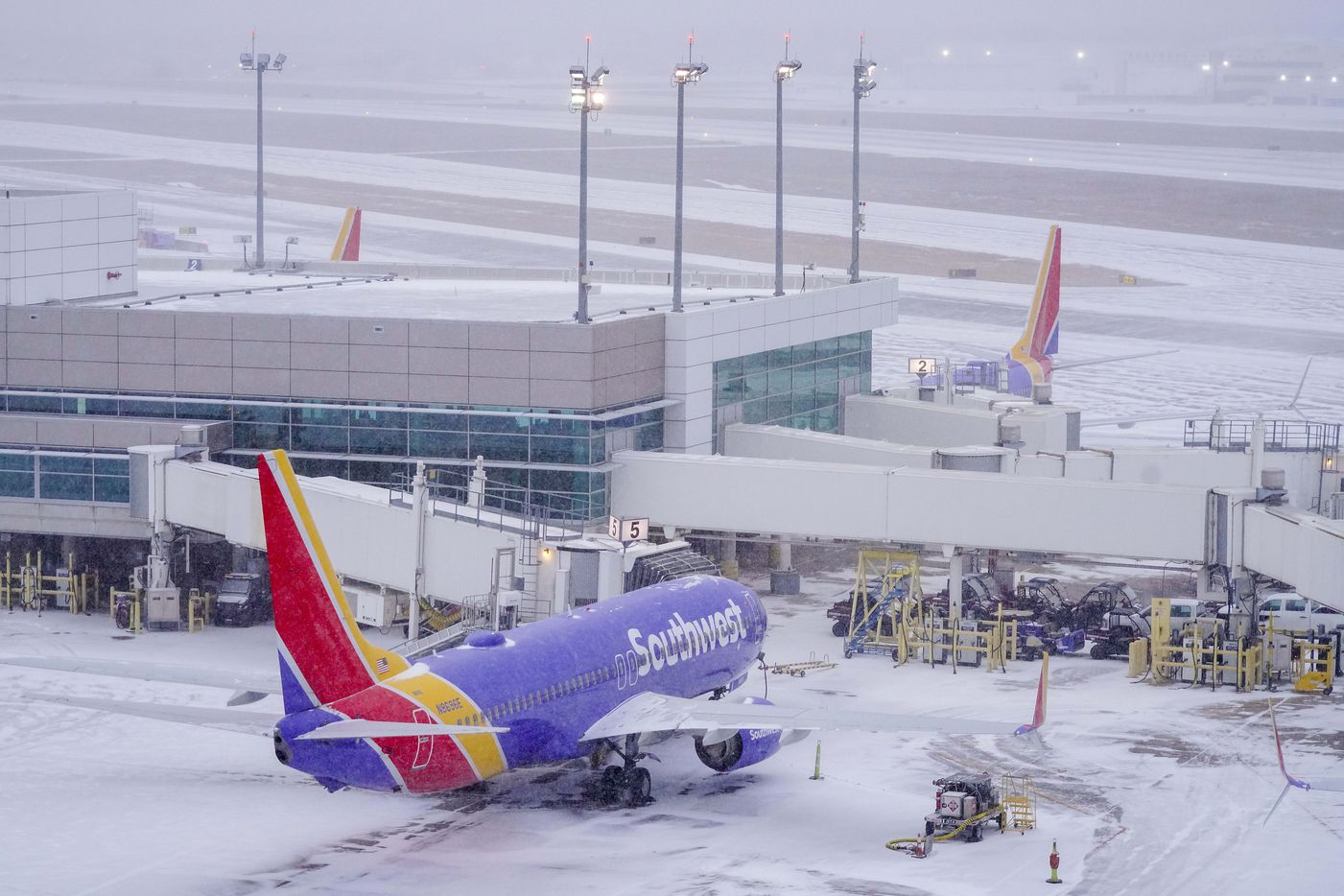 Idle Southwest Airlines planes sits at gates at Dallas Love Field as a winter storm brings snow and freezing temperatures to North Texas on Sunday, Feb. 14, 2021, in Dallas.  By evening all commercial flights were cancelled and all ticket counters were closed at the airport.