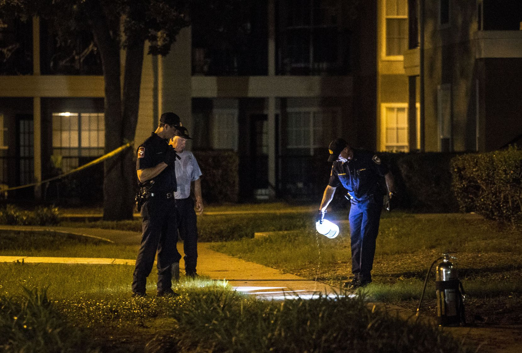 Lewisville police officers clean blood stains from the pavement at Oak Forest Apartments in Lewisville.