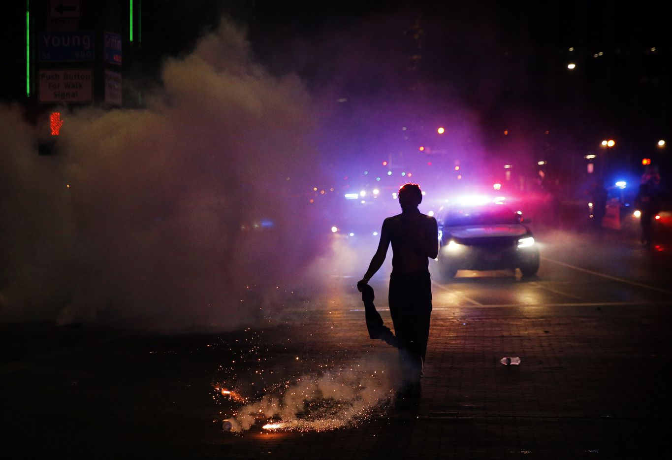 A protestor is nearly hit by a tear gas canister at the intersection of Young St. and S. Griffin St. in downtown Dallas, Friday, May 29, 2020. People were marching in protest of the in-custody death of George Floyd when they confronted Dallas Police tactical officers.