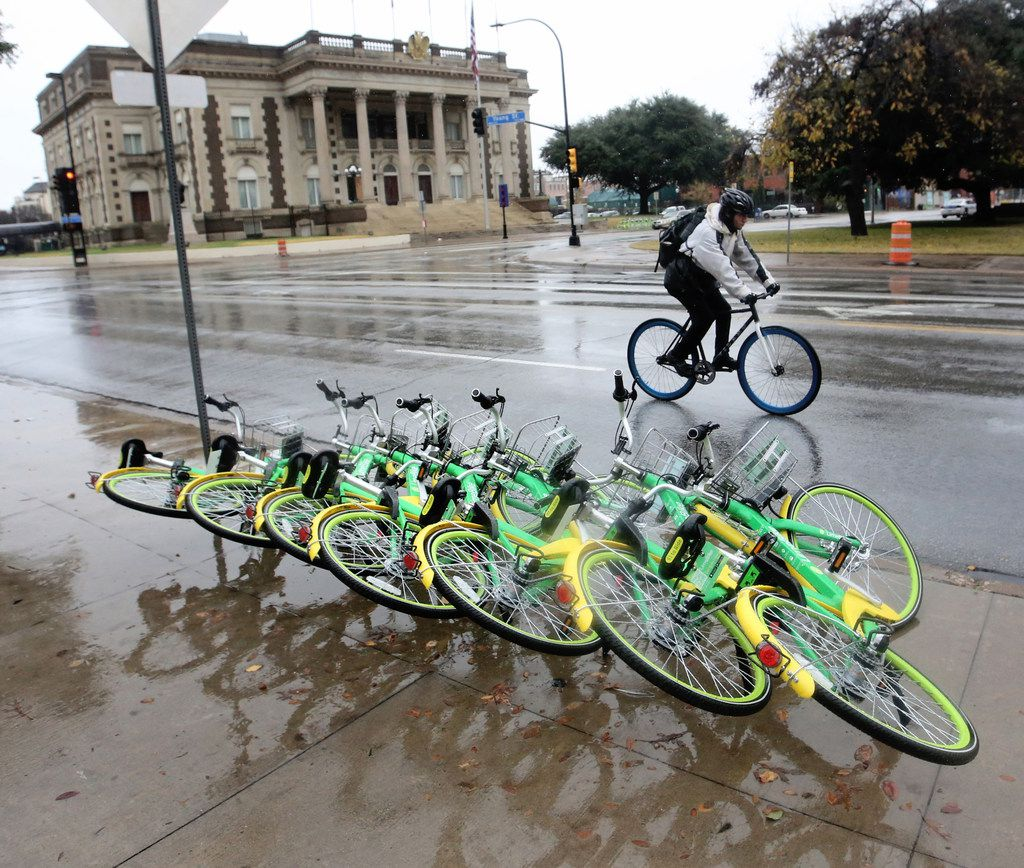 LimeBike rentals lie one on top of another in a line along Young Street in downtown Dallas on Tuesday, Dec. 19, 2017.