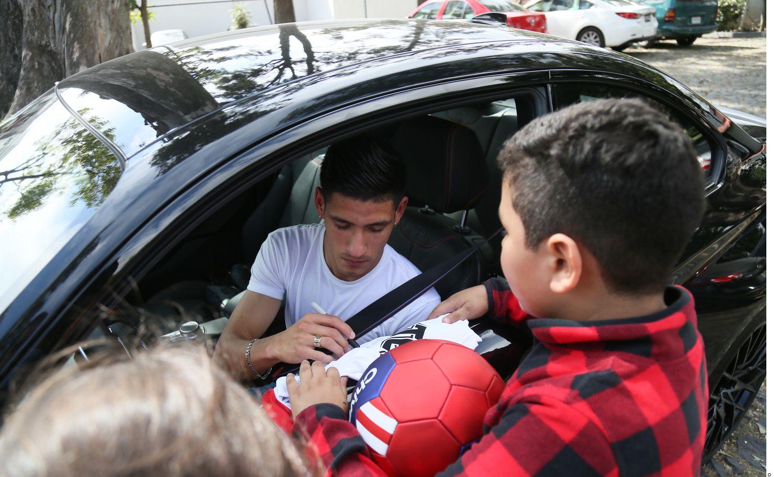 Uriel Antuna firma un autógrafo a un pequeño seguidor de Chivas tras el entrenamiento del equipo en Guadalajara.
