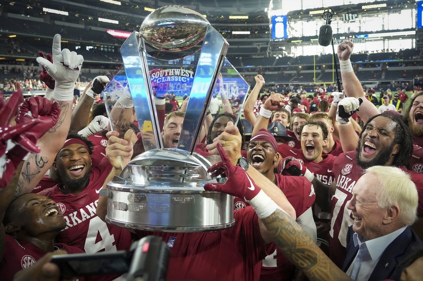 Dallas Cowboys owner and general manager Jerry Jones (bottom right) joins the celebration as Arkansas head coach Sam Pittman lifts the Southwest Classic trophy after a victory over Texas A&M in an NCAA football game at AT&T Stadium on Saturday, Sept. 25, 2021, in Arlington. Arkansas, Jones alma mater, won the game 20-10.