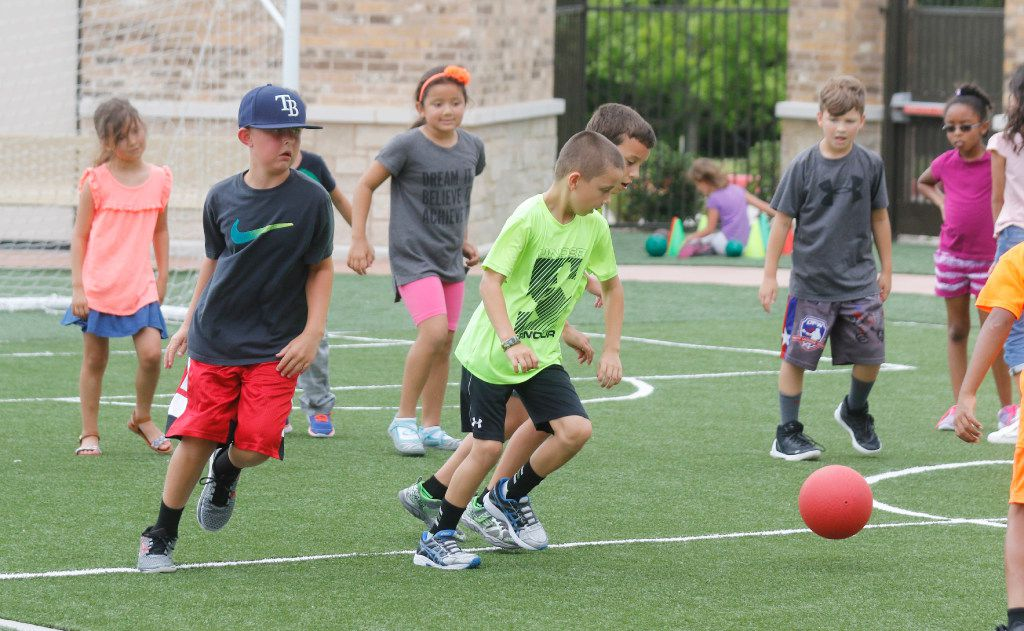 Children play soccer on the Children's Learning Adventure  playground in McKinney. The company is expanding  with new campuses coming to Allen and Flower Mound.