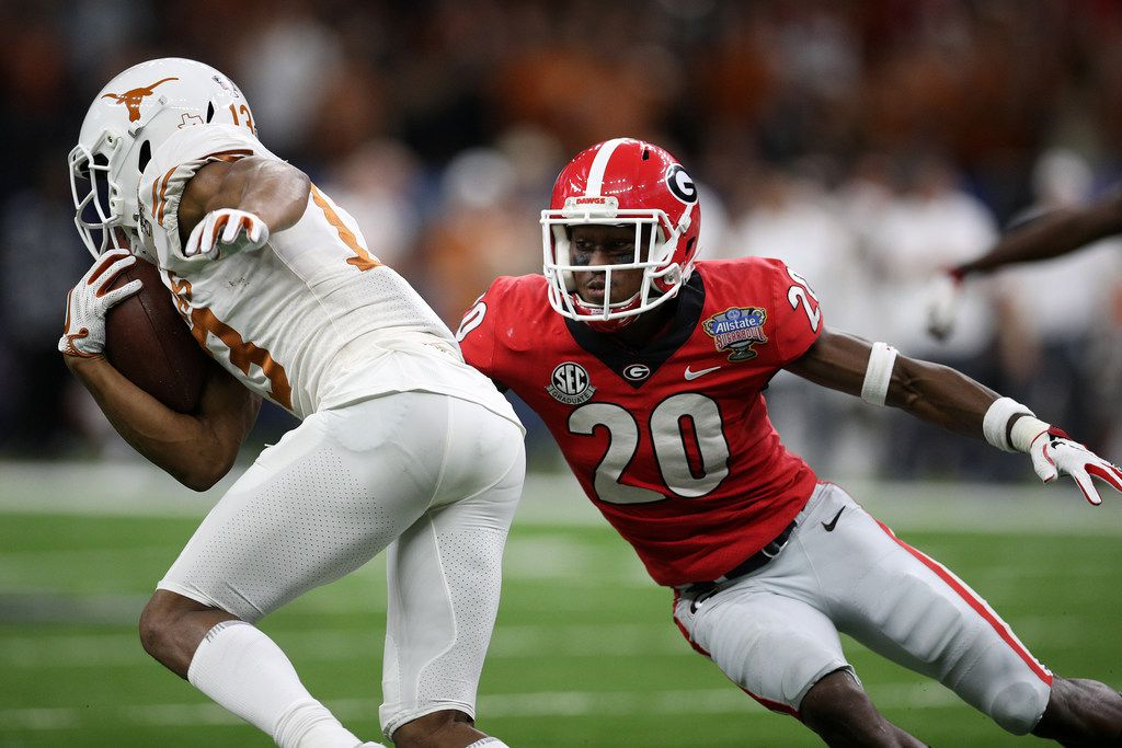 NEW ORLEANS, LOUISIANA - JANUARY 01:  Jerrod Heard #13 of the Texas Longhorns avoids a tackle by J.R. Reed #20 of the Georgia Bulldogs during the Allstate Sugar Bowl at Mercedes-Benz Superdome on January 01, 2019 in New Orleans, Louisiana. (Photo by Chris Graythen/Getty Images)